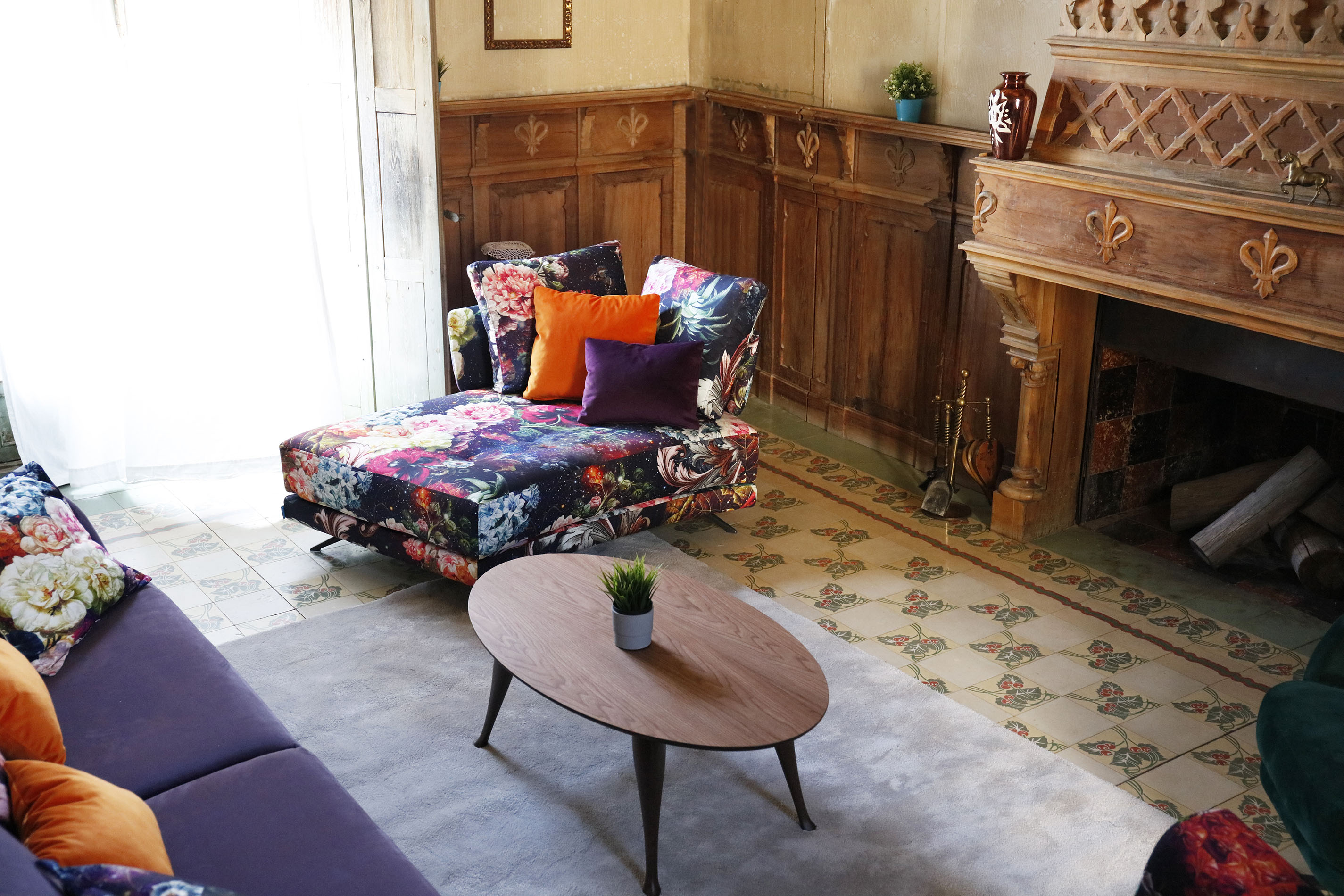 wooden table with black legs, flowerful colorfull sofa set with armchair,