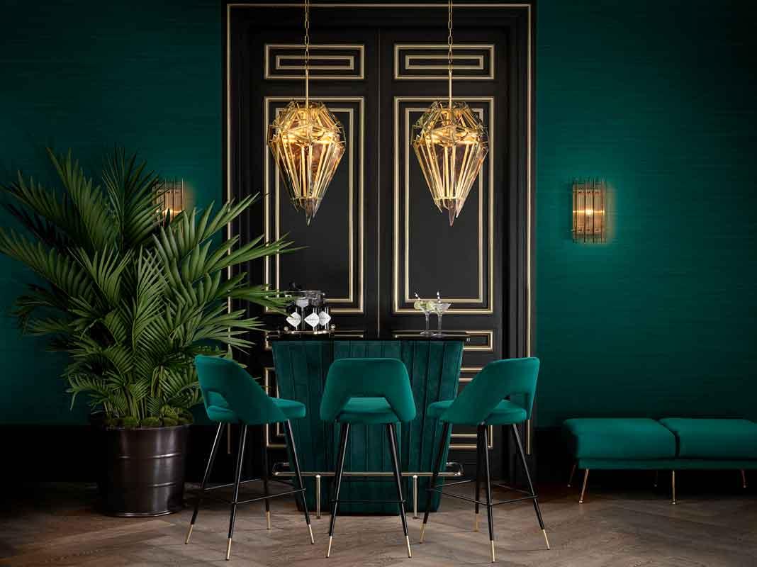 green velvet bar table with matching fabrics barstools with black and gold legs, mpar me idiou ifasmatous stools me mavra kai xrisa podia,