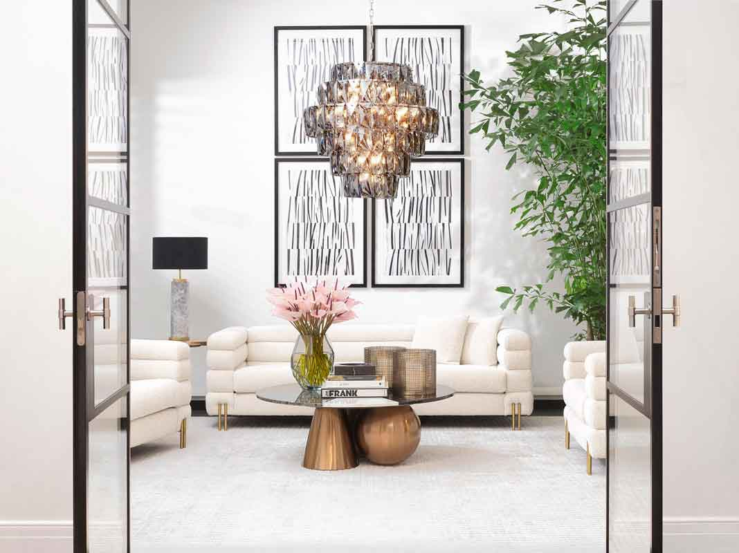 modern table with crystal clear glass top, white comfy elegant modern sofas with gold legs , chandeliers inspo,
